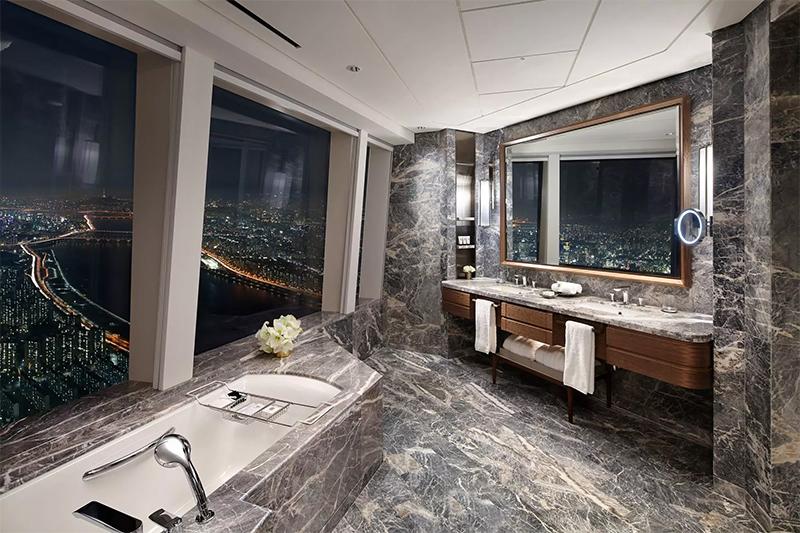 シグニエル ソウルのプレミアスイートのバスルームと窓から望む夜景